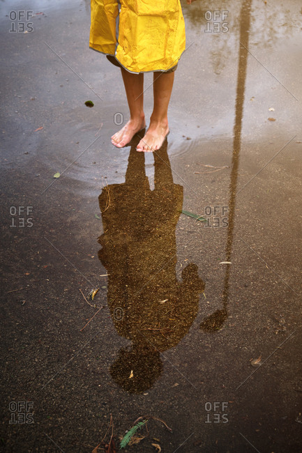 Vertical photo a barefoot boy in a raincoat reflected in a puddle in the middle of a muddy path in the forest