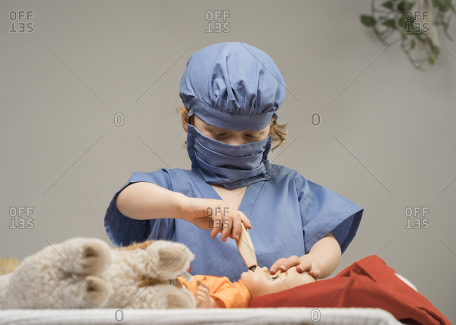 Young child wearing medical PPE examines a baby doll by checking it's temperature with thermometer