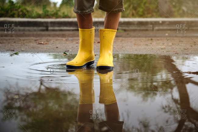 Detail of the legs of a boy with yellow rain boots in a puddle with the reflection in the water in a path in the forest