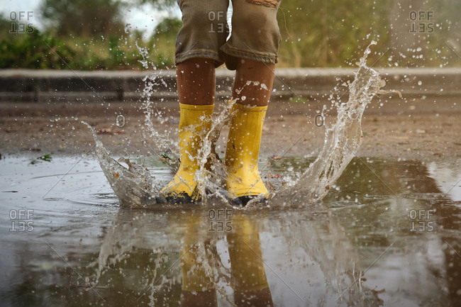 Detail of yellow rain boots hitting a puddle splashing water in a path in the forest