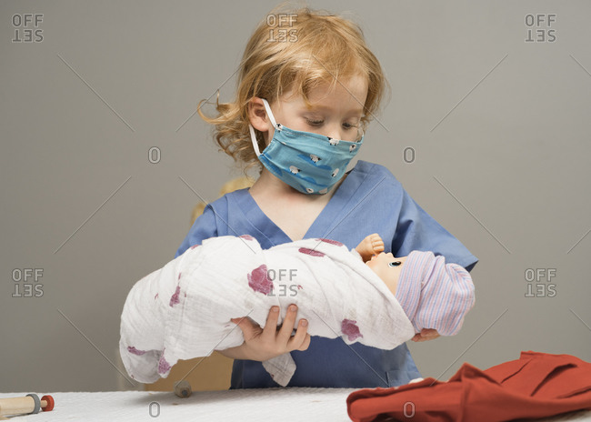 Young child wearing medical PPE holds a swaddled baby doll