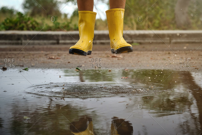 Detail of the legs of a boy with yellow rain boots jumping above a puddle water in a path in the forest