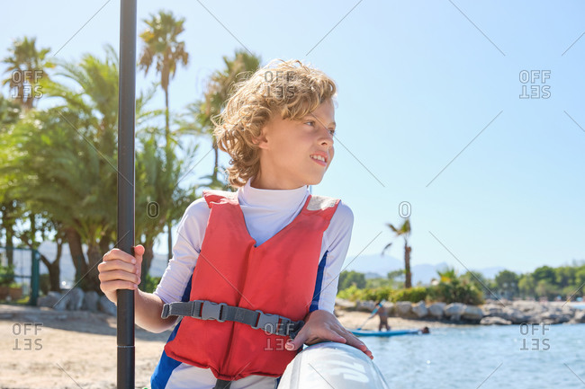 Vertical photo of a blond boy with curly hair looking to a side with distracted expression while wearing a vest leaning against a paddle surfboard and holding the paddle stick on the beach
