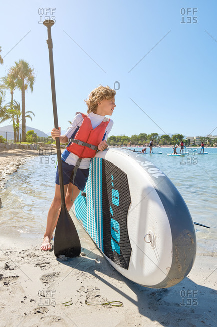 Vertical photo of a blond boy with curly hair looking to a sea with distracted expression while wearing a vest leaning against a paddle surfboard and holding the paddle stick on the beach