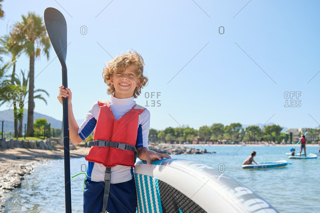Blond boy with curly hair smiling and facing the camera while wearing a vest leaning against a paddle surfboard and holding the paddle stick on the beach