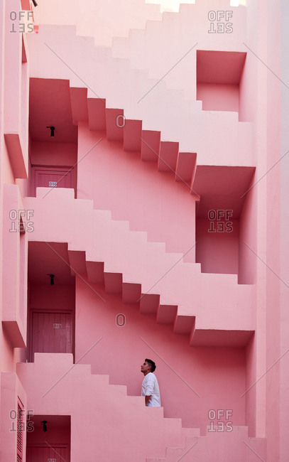 """Calp, Valencian Community, Spain - August 6, 2020: Young Latin man in the """"Muralla Roja"""" in Calpe, Spain"""