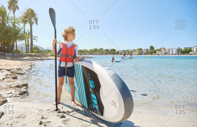 Blond boy with curly hair in a vest facing the sea leaning in a paddle surfboard while holding the paddle stick standing on the beach