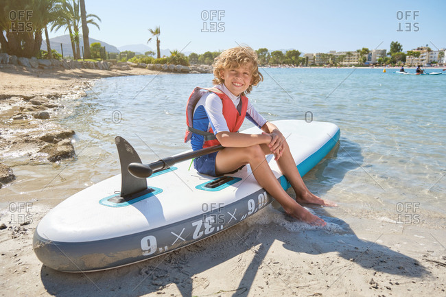 Blond boy with curly hair sitting on top of a paddle surfboard wearing a life jacket while looking at the camera on the beach