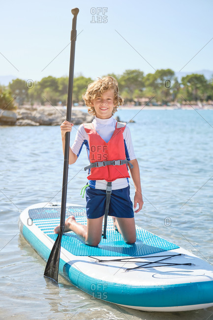 Vertical photo of a blond boy with curly hair and a life jacket kneeling on a paddleboard holding the paddle in his hand while he looks at the camera smiling in the middle of the sea