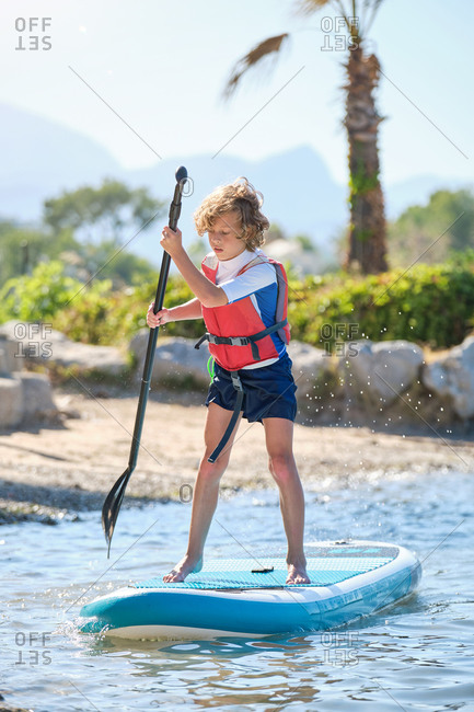 Vertical photo of a blond boy with curly hair and a life jacket rowing standing up on a paddle surfboard in the sea