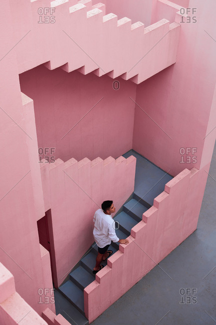 Young Latin man goes down the stairs of a pink building