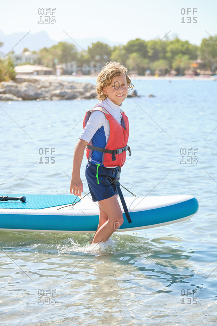 Vertical photo of a blond teenager with curly hair and life vest dragging a paddleboard across the water of the sea while smiling at the camera
