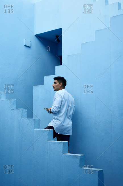 Young Latin man holds his cell phone in a blue building