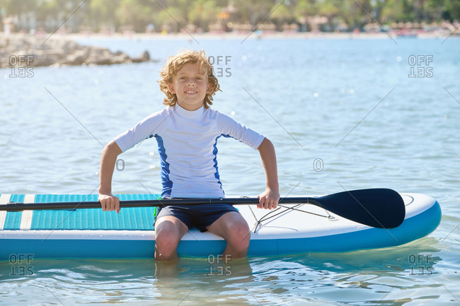 Blond teenager with curly hair sitting on a paddle surfboard in the middle of the water with the paddle in his hands facing the camera