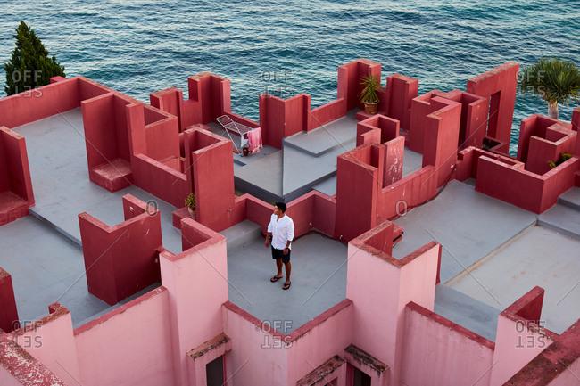 "Calp, Valencian Community, Spain - August 6, 2020: Young Latin man meditative in ""Muralla Roja"" from Calpe, Spain"
