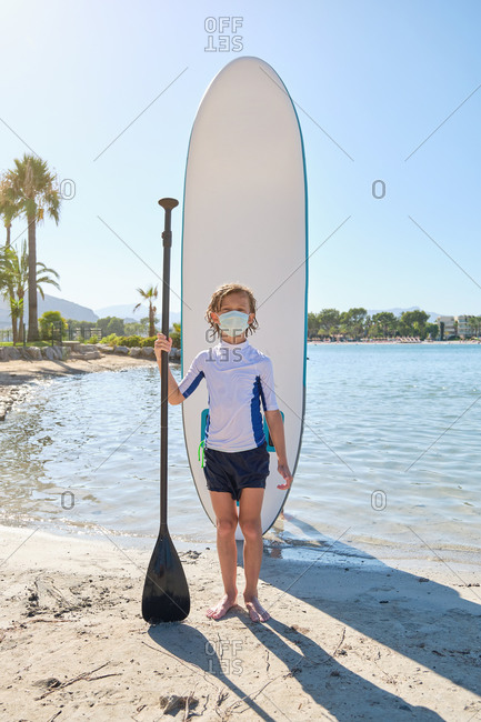 Vertical photo of a child with a mask standing in front of a paddle surfboard stuck in the sand while holding the paddle in his hand and facing the camera