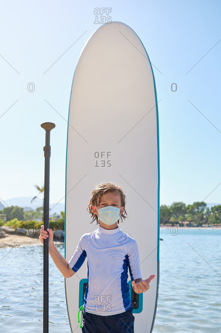Vertical photo of a child with a mask standing in front of a paddle surfboard while holding the paddle in one hand and doing a gesture with the other hand to be cool while facing the camera