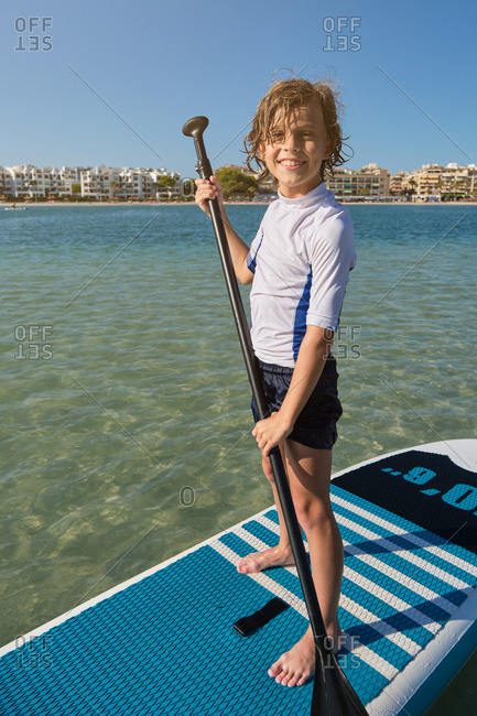 Vertical photo of the portrait of a boy standing on a paddle surfboard with a paddle facing the camera while smiling with the beach with buildings on the background
