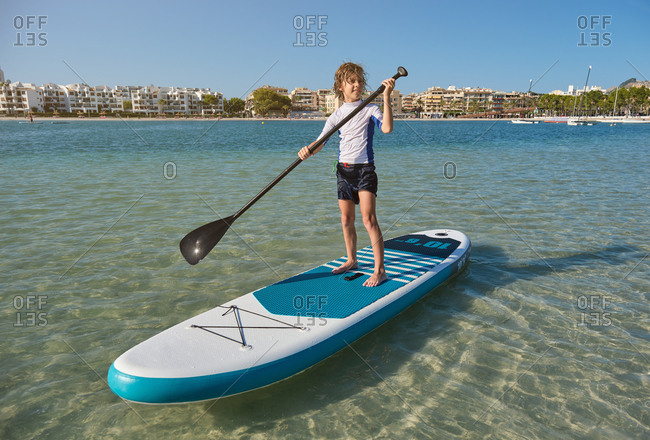 Boy rowing in a paddle surfboard in the middle of the sea water with the beach with buildings on the background