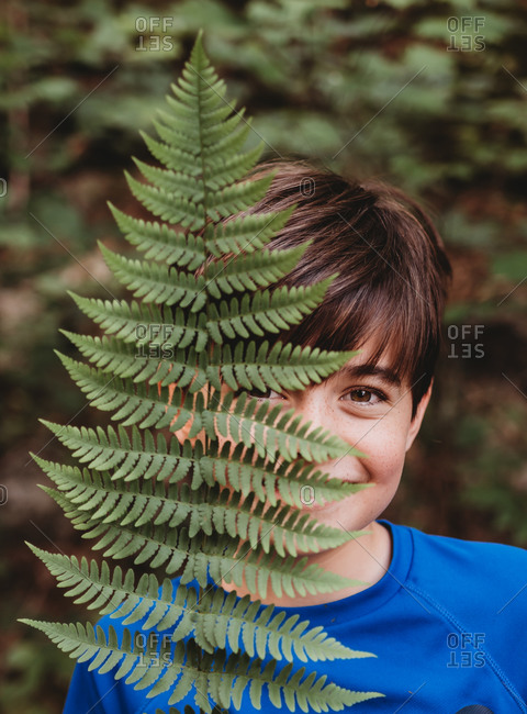 Portrait of young smiling boy covering half his face with fern leaf.