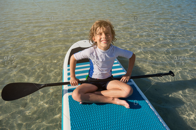 Blonde boy sitting on a paddle surfboard with a paddle floating in the sea while facing the camera with happy expression