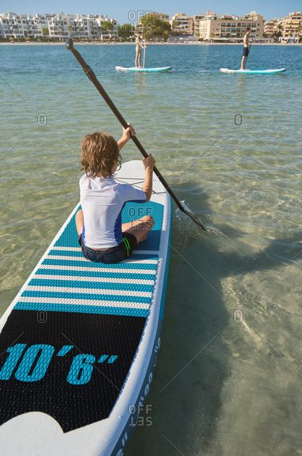 Vertical photo of a blonde boy in his back sitting on a paddle surfboard rowing in the middle of the sea with the beach and other people practicing paddle surf on the background