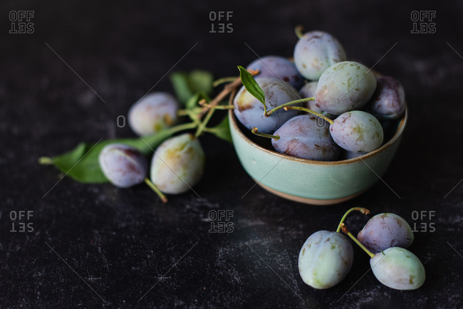 Close up image of a bowl of fresh plums against a black background.