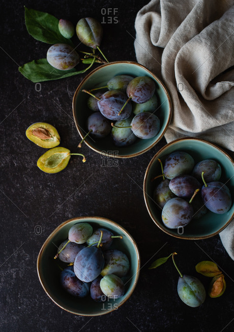 Overhead shot of bowls of fresh plums against a black background.