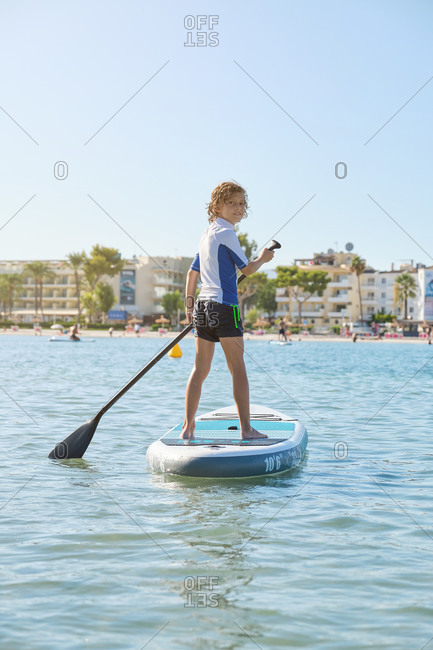 Vertical photo of a blonde boy rowing in a paddle surfboard while turning back to look at the camera in the middle of the sea with the beach on the background
