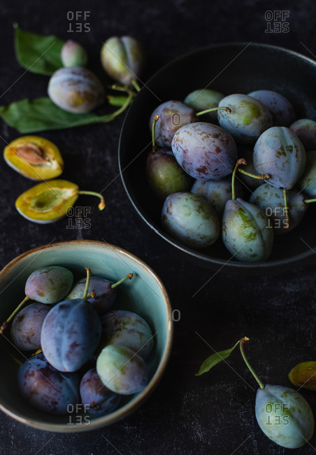 Close up of bowls of fresh plums against a black background.