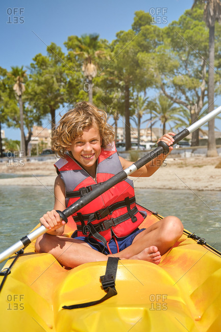 Vertical photo of a blond boy with curly hair and a life jacket rowing and facing the camera in a yellow kayak in the sea with the beach in the background on a sunny day