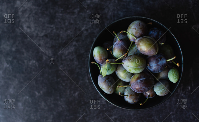 Overhead shot of a bowl of fresh plums against a black background.
