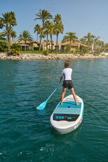 Vertical photo of a blond boy in his back standing on a paddle surfboard paddling in the middle of the sea with a palm beach in the background