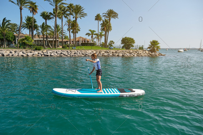 Blond boy standing on a paddle surfboard rowing in the middle of the sea with a palm beach in the background