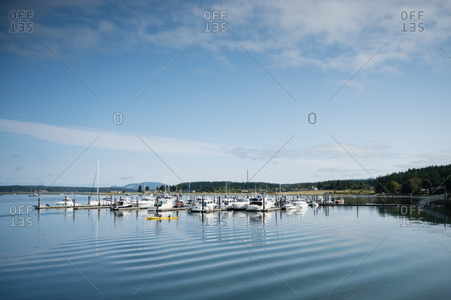 United States, Washington, Lopez Island - August 2, 2019: Sailboats and a yellow kayak under the blue sky at the Lopez Island harbor