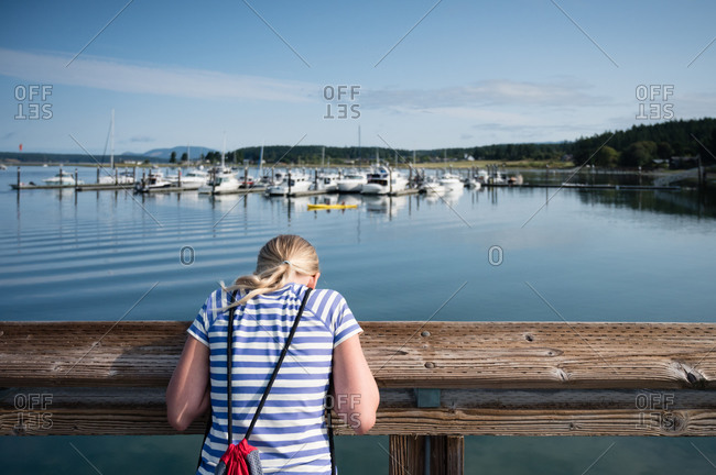 Young girl looking off a dock at the Lopez Island harbor in WA