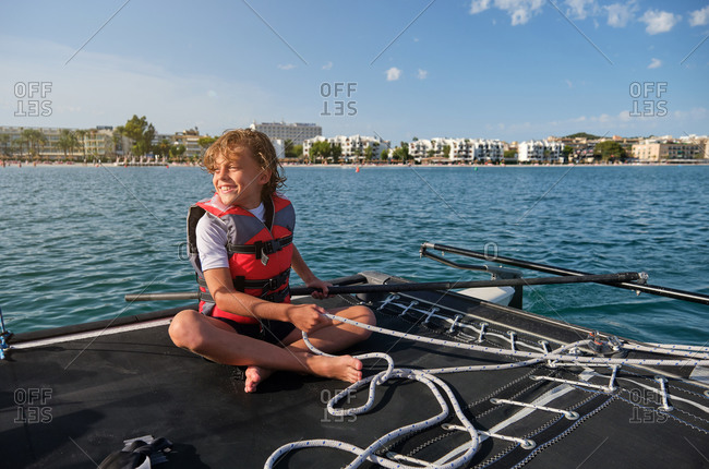 Blond boy with life jacket sitting in a boat holding the rudder and a rope with the shore far away in the background