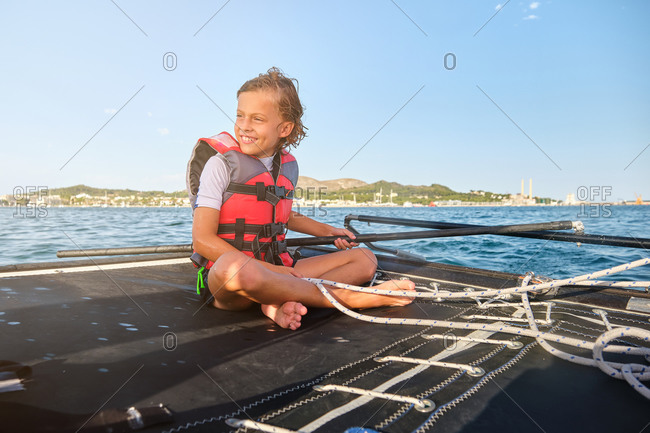 Blond kid with life jacket sitting in a boat holding the rudder and a rope to drive the boat while smiling with the shore far away in the background