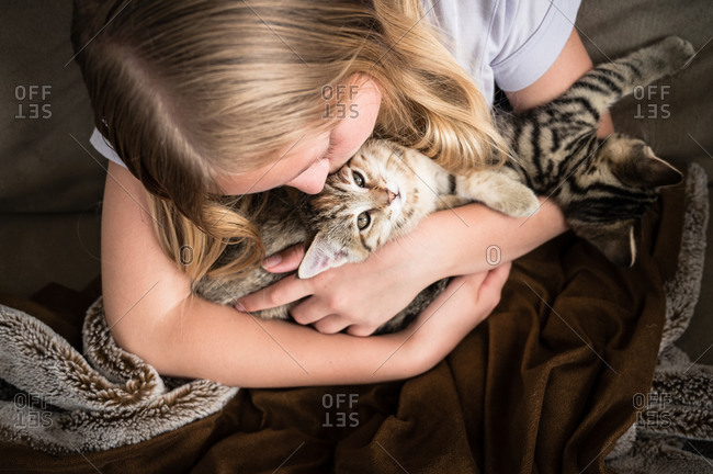 Young Girl Looking Down Holding Kittens on Brown Blanket