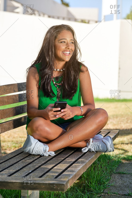 Vertical photo of a brunette girl sitting on a bench in summer clothes using her mobile phone while she looks smiling to one side in a park with buildings behind