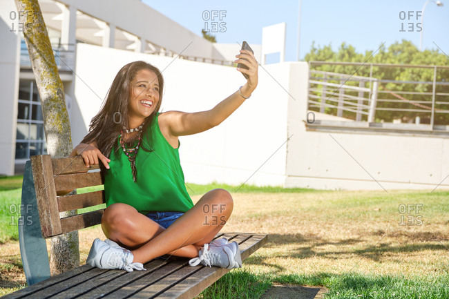 Brunette girl sitting on a bench in summer clothes making a selfie with her mobile phone while she looks at the camera smiling in a park with buildings behind