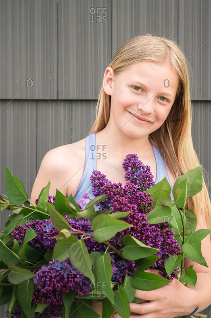 Tween Girl Holding Bunch of Purple Lilac Flowers and Smiling