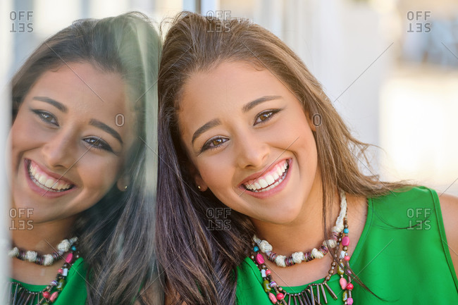 Young brunette woman smiling distractedly as she rests her head on a glass with her image reflected in symmetry on the street
