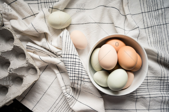 Eggs Nestled in White Bowl on White and Black Tablecloth with Carton