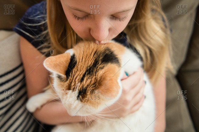 Close Up of Young Girl Kissing Calico Cat at Home