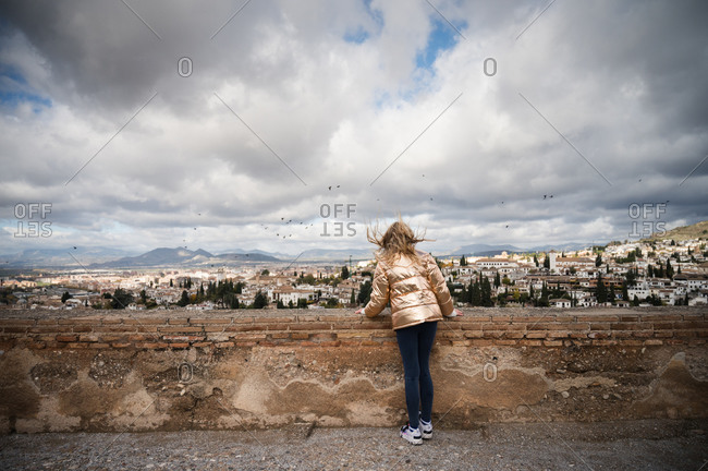 Girl Looking Out at Granada Spain With Wind and Dramatic Clouds