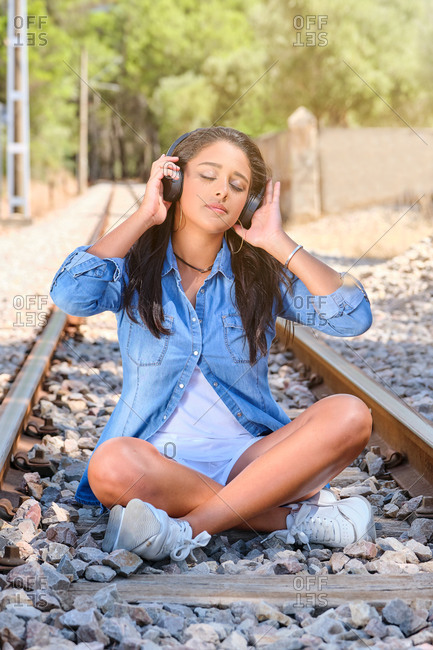 Vertical photo of a young brunette woman listening to music with wireless helmets with her eyes closed, sitting on a train track