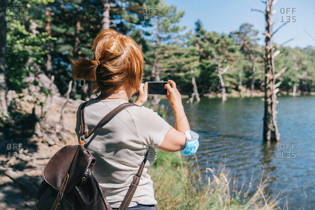 Mature woman with a medical face mask taking a photo with a mobile phone to a lake