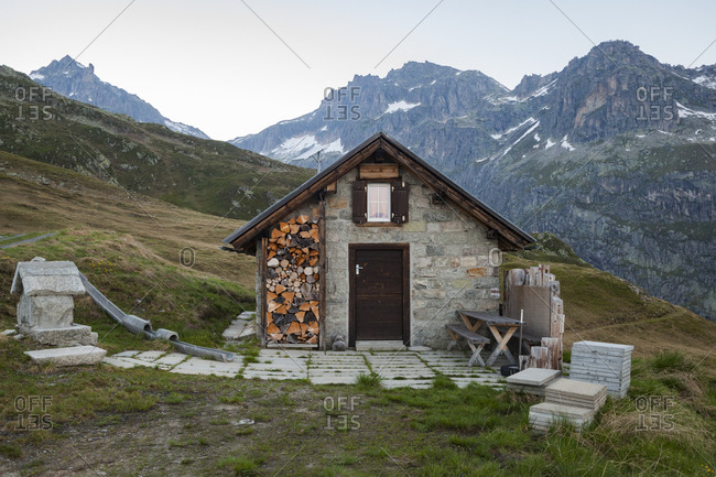 Lone cabin with wood pile above Realp, Uri, Switzerland