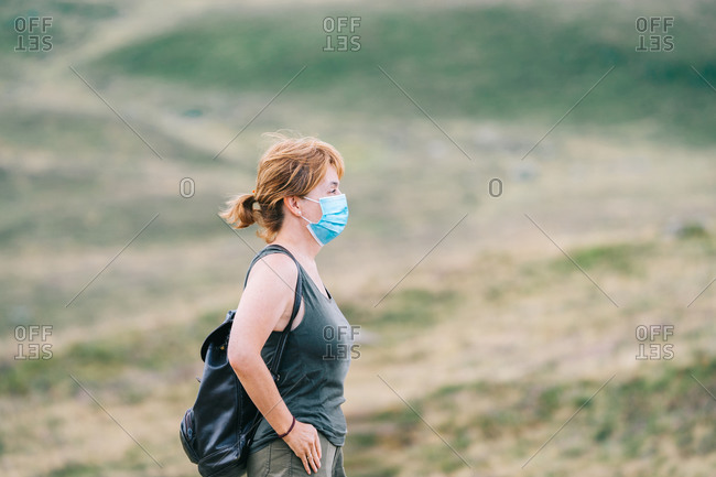 Mature traveler woman in profile with medical face mask